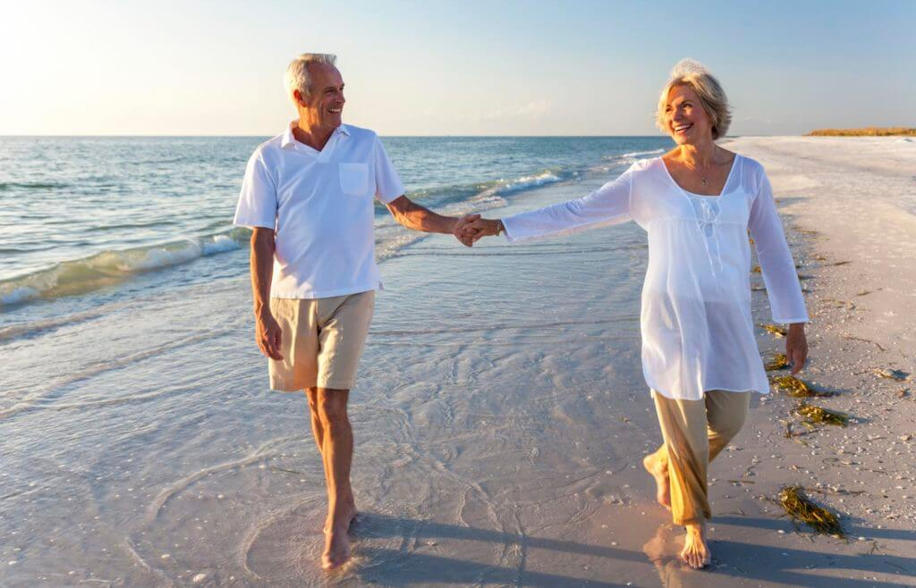 senior couple walking on beach holding hands
